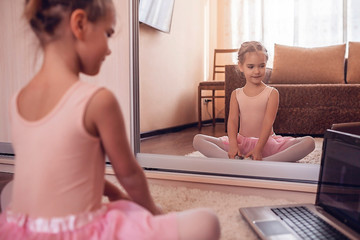 Young ballerina practicing classic choreography during online class in ballet school, self-isolation