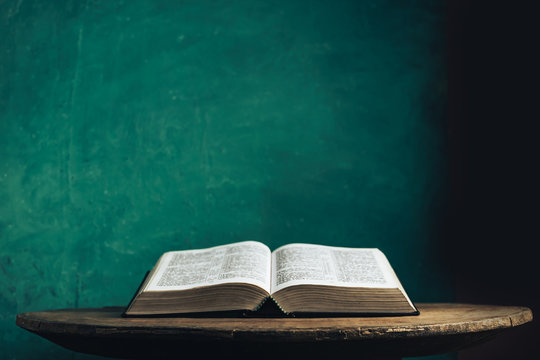 Open Holy Bible on a old round wooden table. Beautiful green wall background.