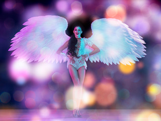 Young female dancer with white angel's wings in purple blue neon light on black background in...