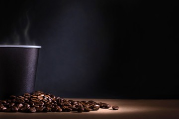 Black disposable cup of coffee with smoke and scattered coffee beans on dark background. Space for text