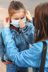 A mother helps her daughter wear a medical mask to protect Cvid 19 or a coronary virus outbreak situation. Covid 19, Corona, Viral outbreak, healthcare and medicine, family concept.