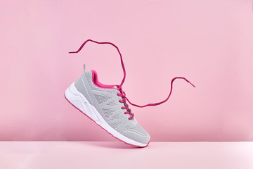 Pair of fashion stylish sneakers with flying laces, Running sports shoes on pink background Wall mural