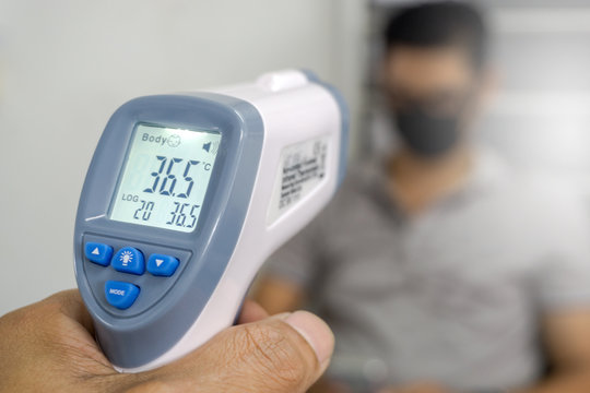 Hand holding infrared thermometer to measuring temperature on blurred asia people with face mask on background. Covid flu screening 19 concept.