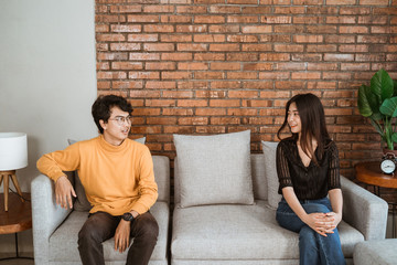 couple separating while sitting on a couch. social distancing concept