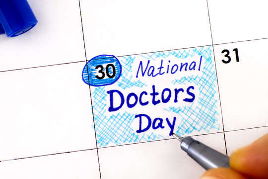 Woman fingers with pen writing reminder National Doctors Day in calendar.
