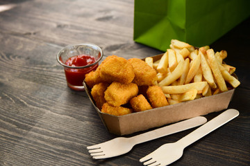 food delivery service. hot chicken nuggets and fries. take out food in a single use packaging made of recycled cardboard. takeaway food . selective focus and copy space