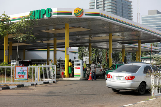 Cars queue to buy petrol at the NNPC Mega petrol station in Abuja