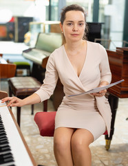 Tuinposter Muziekwinkel Female assistant or customer at piano music store
