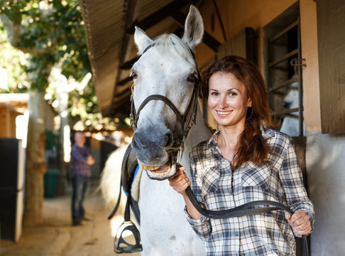 Female farmer standing  with white horse  at stable outdoor