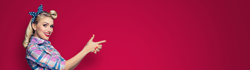 Young smiling woman pointing at something. Girl in pin up cloth, showing some product or copy space for text. Retro fashion and vintage. Red color background. Wide horizontal banner composition.