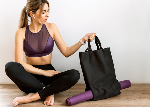 Fitness sporty girl wearing fashion sportswear over white wall, outdoor sports, urban style. holding a bag with yoga mat
