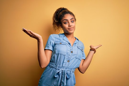 Young beautiful african american girl wearing denim dress standing over yellow background clueless and confused expression with arms and hands raised. Doubt concept.