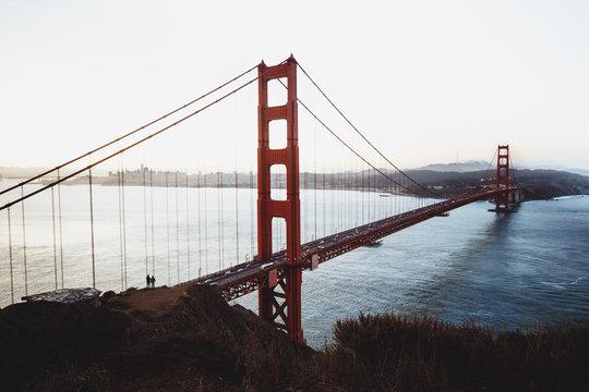 Sonnenaufgang an Golden Gate Bridge mit zwei Personen auf Hügel im Vordergrund