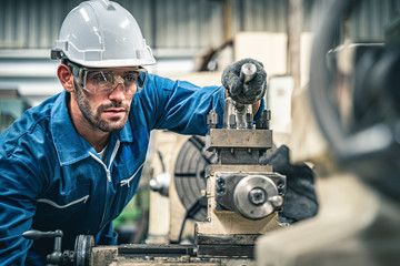 Male engineer in blue jumpsuit and white hard hat operating lathe machine.