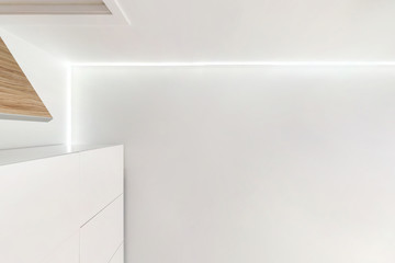 suspended ceiling with led lightspot lamps and drywall construction in empty room in apartment or house. Stretch ceiling white and complex shape. looking up