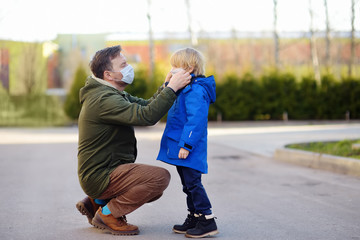 Mature man wearing a protective mask puts a face mask on a his son in airport, supermarket or other...