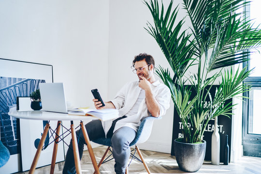 Cheerful freelancer using mobile phone in creative hall