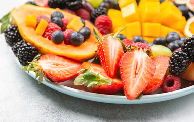 Wall Mural - Colorful fruit platter pomegranate papaya oranges grapes berries on plate on white, selective focus