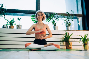 Smiling woman sitting in lotus position and looking at camera