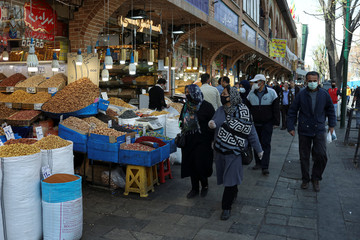 People wear a protective face masks, amid fear of coronavirus disease (COVID-19), as they walk at the Grand bazar, ahead of the Iranian New Year Nowruz, March 20, in Tehran