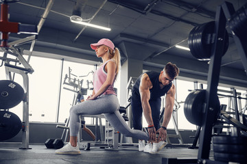Side view of focused and motivated sporty young blonde girl in sportswear doing legs exercises while handsome muscular personal trainer monitoring her in the gym.