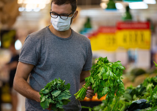 Alarmed male wears medical mask against coronavirus while grocery shopping in supermarket or store- health, safety and pandemic concept - young man stockpiling food in fear of covid-19