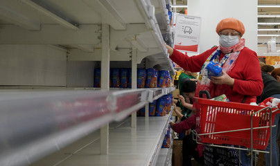 A woman, wearing a protective mask, holds a pack of buckwheat from a new delivery, next to empty shelves in a section for cereals and groats, in a supermarket in Moscow