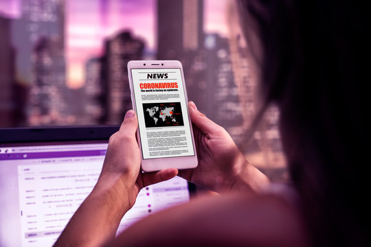 Coronavirus News. Woman in the office with smartphone in her hands reading about covid-19 virus. Online newspaper page in the screen.