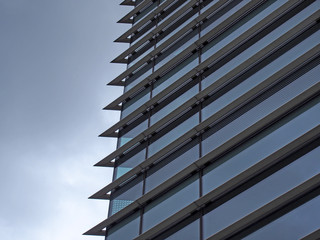 corner of a futuristic building with steel geometric lines and blue glass windows reflecting a blue sky