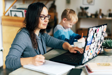 Concept of work from home and home family education. Mom and son are sitting at the desk. Business woman works on the Internet in a laptop, a child writes in a notebook.