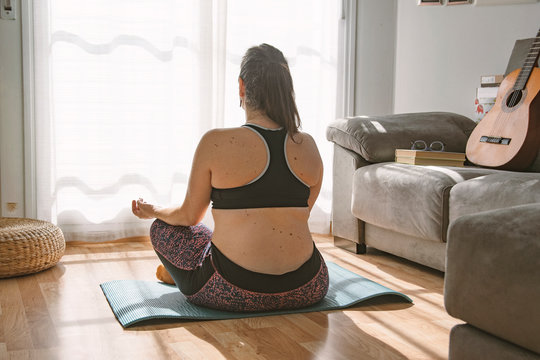 Young curvy caucasian woman in lotus asana position doing yoga at home in the living room. Empty copy space for Editor's content.