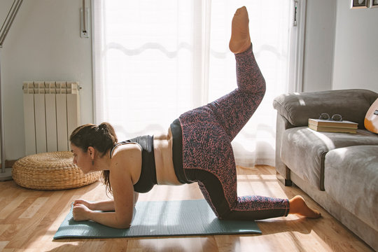 Young curvy caucasian woman doing some pilates at home in the living room. Empty copy space for Editor's content.