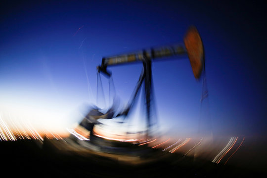 A long exposure image shows the movement of a crude oil pump jack in the Permian Basin in Loving County