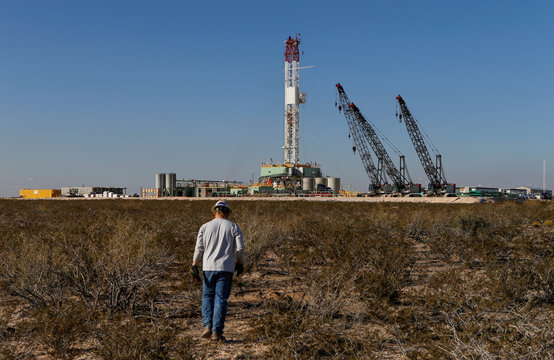 An oil worker walks towards a drill rig after placing ground monitoring equipment in the vicinity of the underground horizontal drill in Loving County