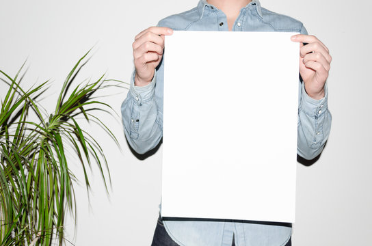 A3 Poster Mock-Up - Man in a denim shirt holding a poster on a white background. Hipster Aesthetic