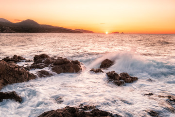 Waves crashing onto rocky Corsica coastline at sunset
