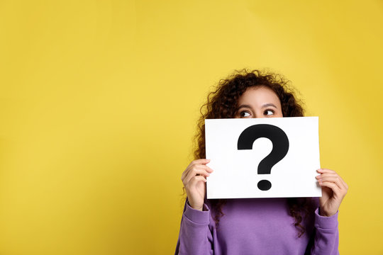 African-American woman with question mark sign on yellow background. Space for text