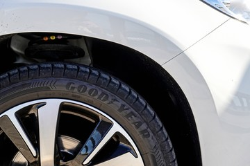 The detail of a brand new GoodYear tyre on a white Peugeot SUV.