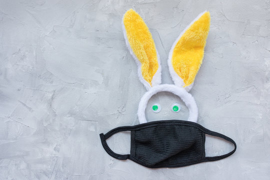 Easter during coronavirus concept. Bunny ears and mask on gray background. COVID-19 outbreak, celebration and stay home concept. Top view, flat lay, copy space