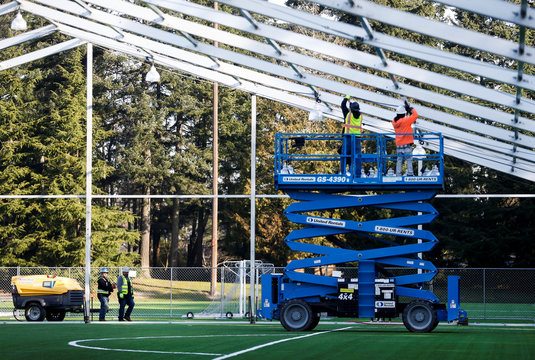 Workers install lights on the ceiling of a 200-bed temporary field hospital for people exposed to, at risk of exposure, or becoming ill with coronavirus at the Shoreline Soccer Field during the outbreak of coronavirus disease (COVID-19) in Shoreline