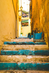 Deurstickers Yellow Walls and Teal Blue Green Stairs on a Small Passage in Alicante Spain