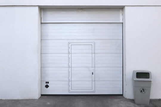 closed white garage or warehouse front with door entrance and a bin for recycling