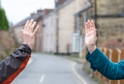 Social distancing wave. Recommended greeting to avoid the spread of coronavirus. Two friends meet, instead of greeting with a hug or handshake, they stay apart and wave to each other.