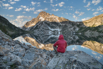 Adult male hiker in red jacket admired the view of Mount Regan mirrored in still waters of Sawtooth Lake at sunrise. Sawtooth Mountains Wilderness Idaho; Adult male hiker in red jacket at Sawtooth Lake. Sawtooth Wilderness Idaho. Idaho. United States