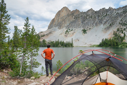 Adult male enjoying the view at a backcountry camp at Alice Lake Sawtooth Mountains Idaho; Adult male in red shirt enjoying the view at a backcountry camp at Alice Lake Sawtooth Mountains Idaho. Idaho. United States