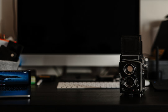 Vintage film camera on a desk in front of a modern computer