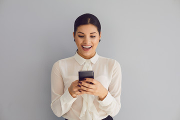 Using the phone on social networks. Hispanic young happy woman typing sms in mobile smiling while standing on gray background. Wall mural