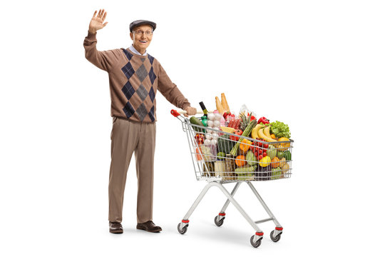 Mature gentleman waving and standing with a shopping cart