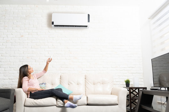 Woman Turning on Air Conditioner At Home