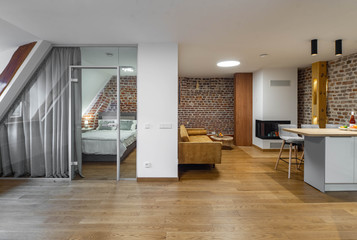 Modern contemporary interior of studio apartment. Private house. Brick wall. Kitchen set.